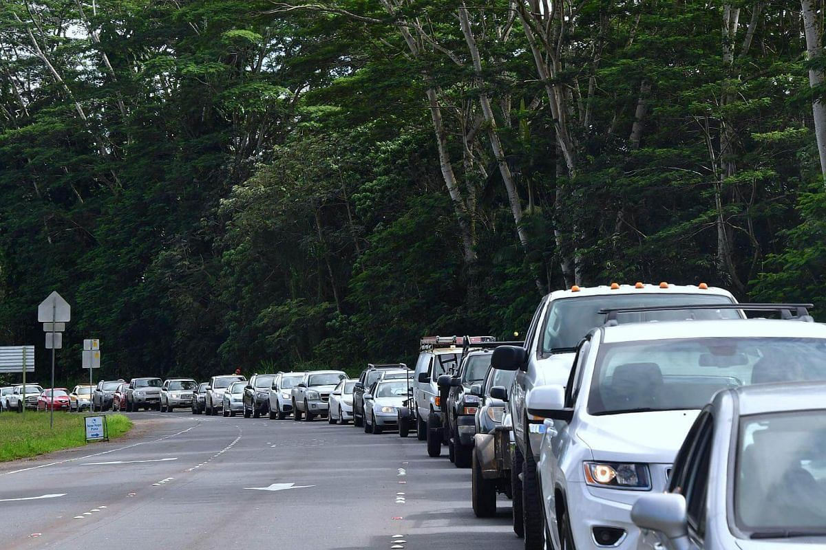 A line of vechicles head for the intersection of Pahoa and Kapoho Roads as evacuees are allowed to return to their Leilani Estates homes to gather belongings and exit, on May 6, 2018.