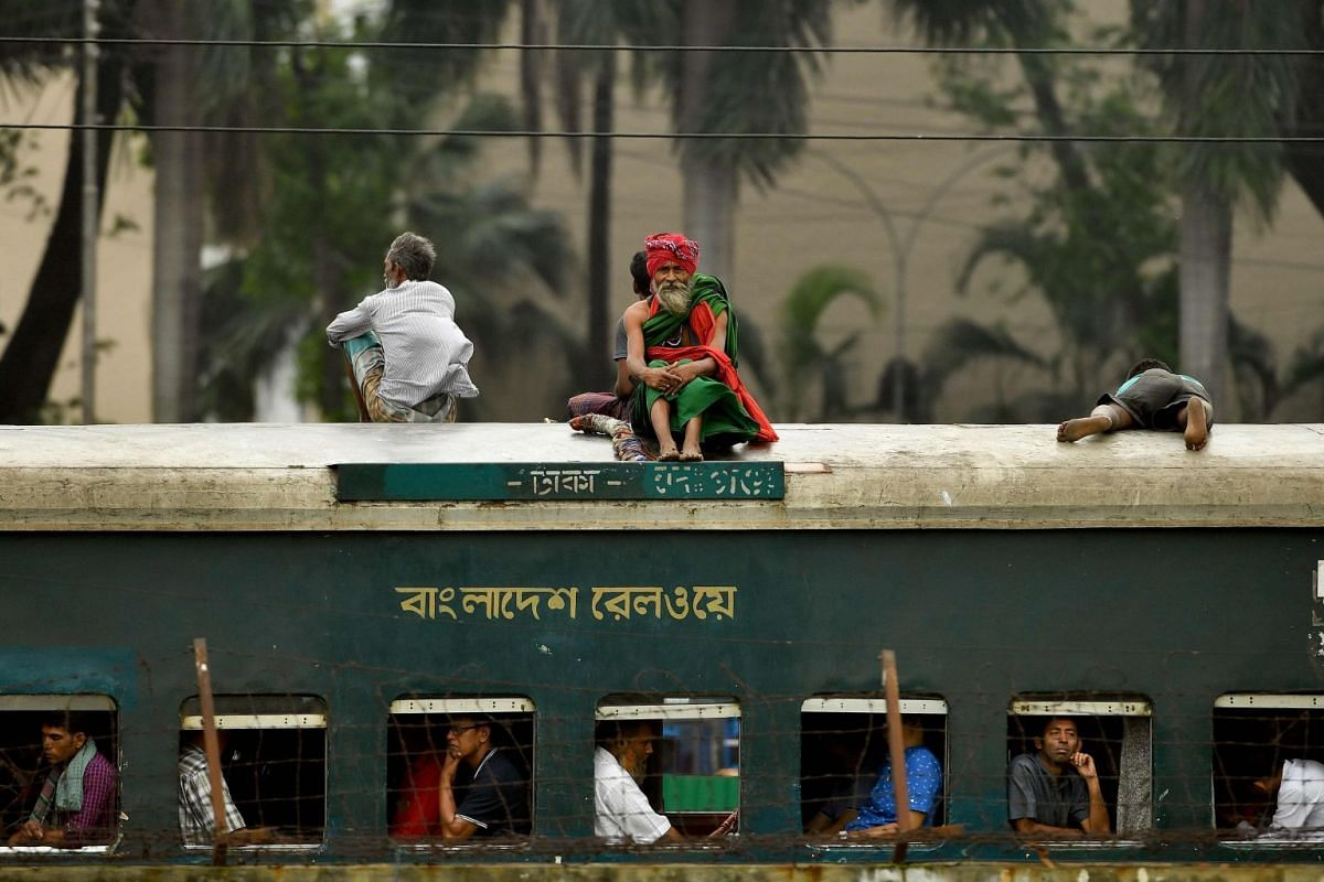 This handout photo taken and released on May 7, 2018, by the Asian Tour shows Bangladeshi passengers riding atop a train near the 14th hole pictured during an official practice round ahead of the AB Bank Bangladesh Open at the Kurmitola Golf Club in