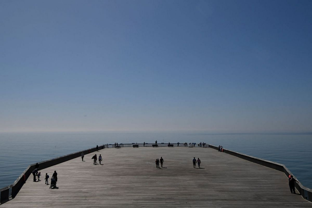 Visitors enjoy the weather as they walk on Hastings Pier at Hastings, Britain, May 7, 2018. PHOTO: REUTERS