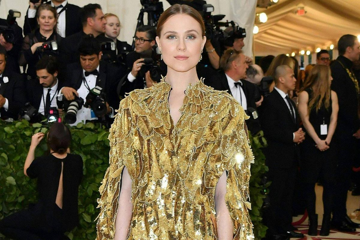 Actress Evan Rachel Wood shimmers in a spectacular gold gown festooned with elaborately embroidered feathers.