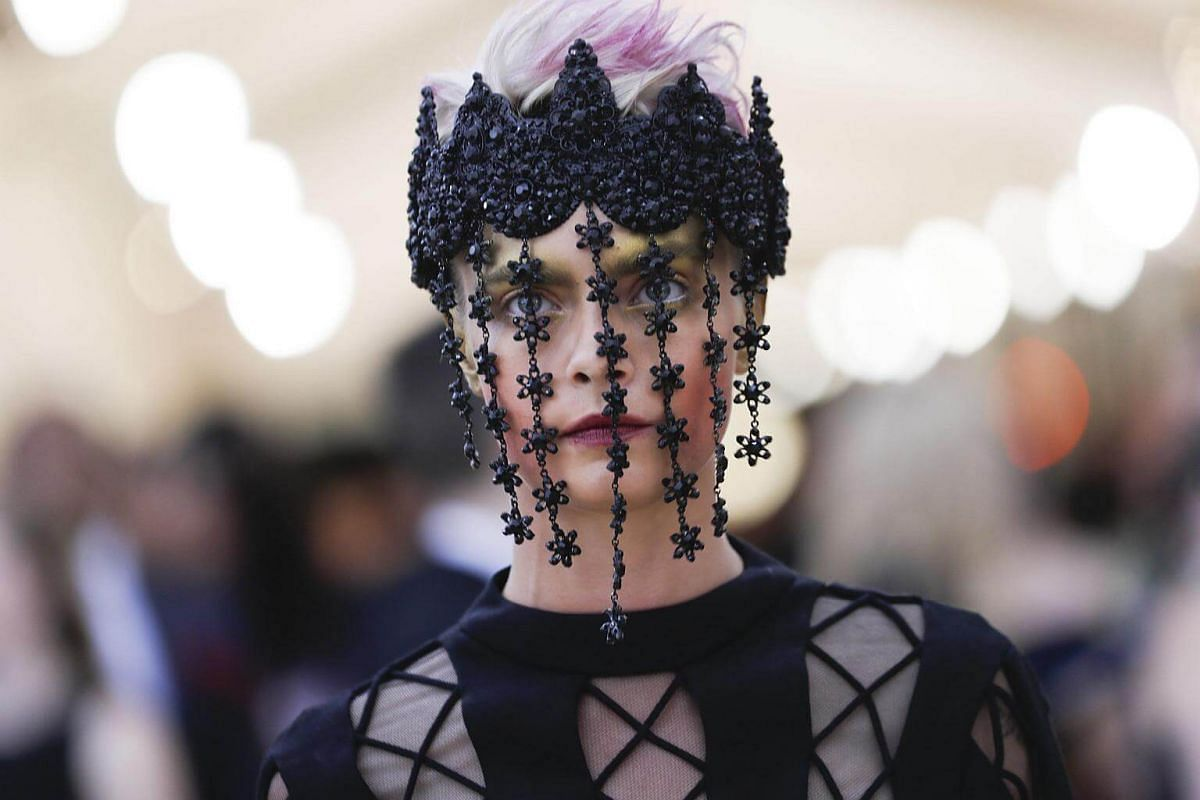 Actress-model Cara Delevingne's white-pink punk hair and embellished headpiece brings a Gothic funk edge to the evening.