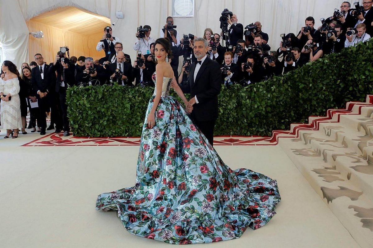 George and Amal Clooney (and their curtains) arrive at the Met Gala. The front of Amal's outfit includes Flashdance satin pants. Trust us, you don't want to see that.