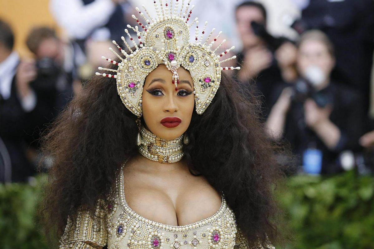 Rapper Cardi B raids a bead workshop for her dramatic headgear, which matches the oversized choker, which matches her dress. Sometimes, too much is just too much.