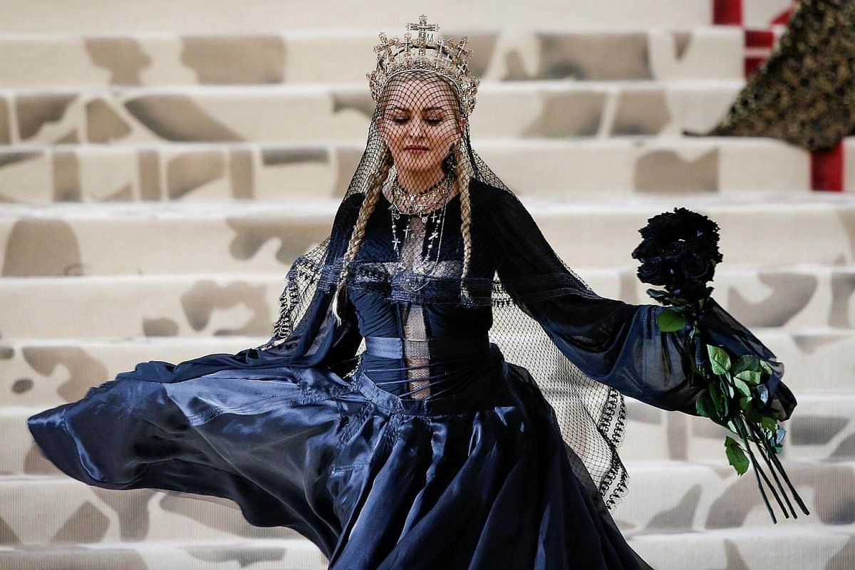 Madonna, queen of pop, shows the young 'uns how to do it right. Her stark, deep navy blue gown, with discreetly strategic see-through inserts, is matched with playful pigtails and black roses. But the crowning statement, literally, is her headgear, a