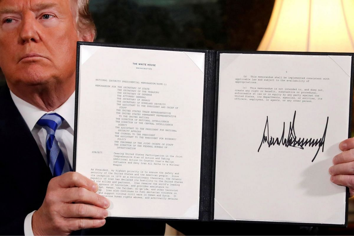 U.S. President Donald Trump holds up a proclamation declaring his intention to withdraw from the JCPOA Iran nuclear agreement after signing it in the Diplomatic Room at the White House in Washington, U.S. May 8, 2018. PHOTO: REUTERS