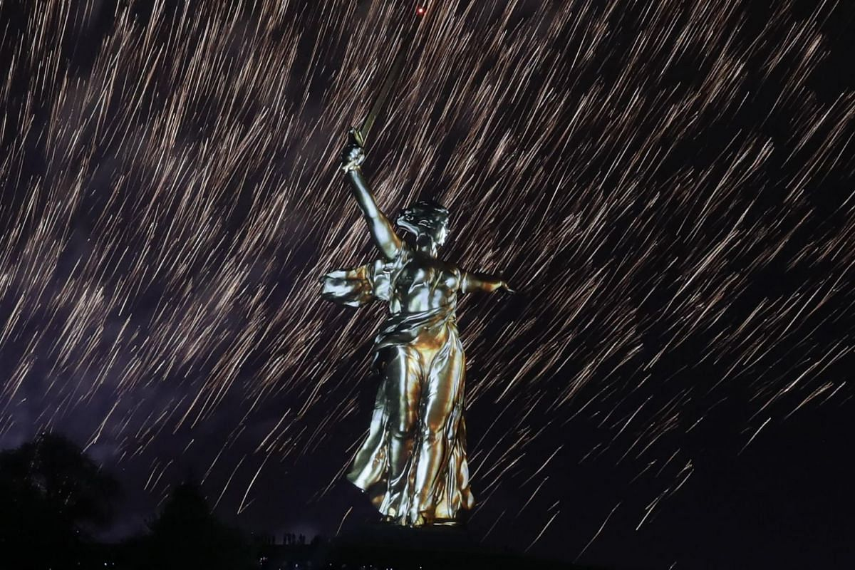 Fireworks explode over the statue Motherland Calls, a World War Two memorial located on the top of Mamayev Kurgan hill, during a light and laser show dedicated to the 73rd anniversary of the victory over Nazi Germany in World War Two, in Volgograd, R