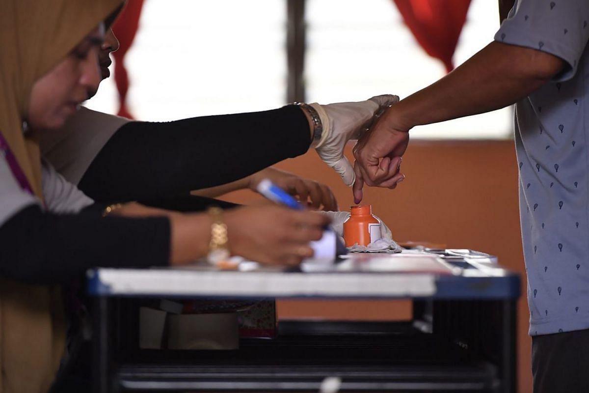 A voter dipping his finger into a bottle of ink at SMK Pasir Gudang 3, Jalan Jati, Taman Air Biru, Pasir Gudang, Johor, Malaysia, on May 9, 2018.