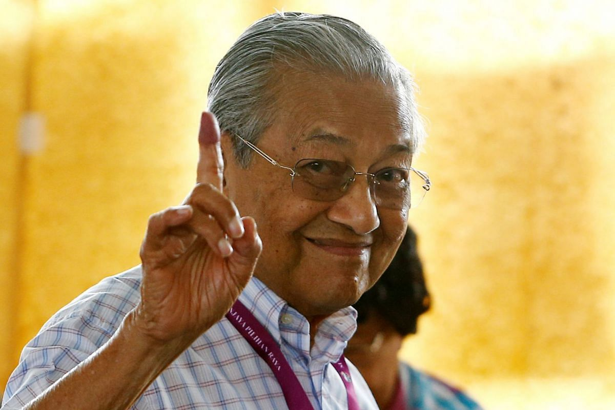 Mahathir Mohamad, former Malaysian prime minister and opposition candidate for Pakatan Harapan (Alliance of Hope), holds up an ink-stained finger as he votes during the general election in Alor Setar, Malaysia, on May 9, 2018.