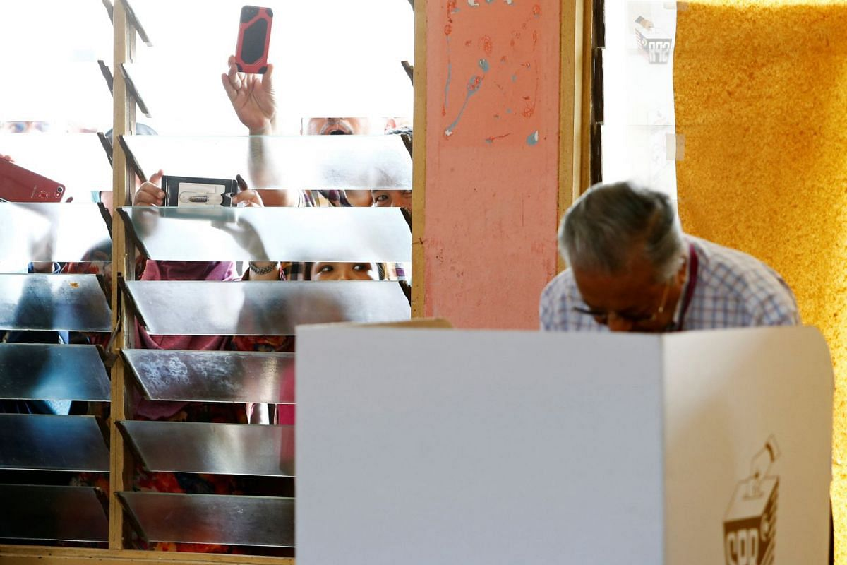 Onlookers take pictures of Mahathir Mohamad, former Malaysian prime minister and opposition candidate for Pakatan Harapan (Alliance of Hope), as he votes during the general election in Alor Setar, Malaysia, on May 9, 2018.