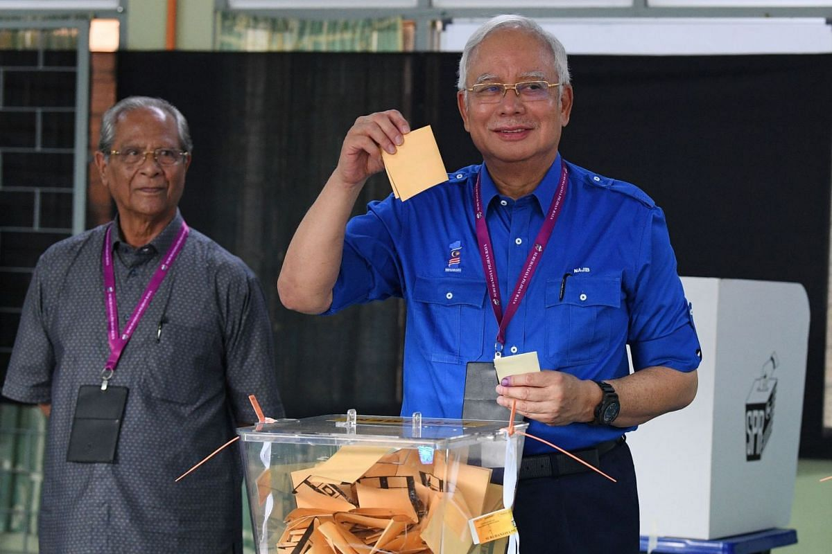 Malaysian Prime Minister Najib votes at a polling station during the 14th general elections in Pekan on May 9, 2018.