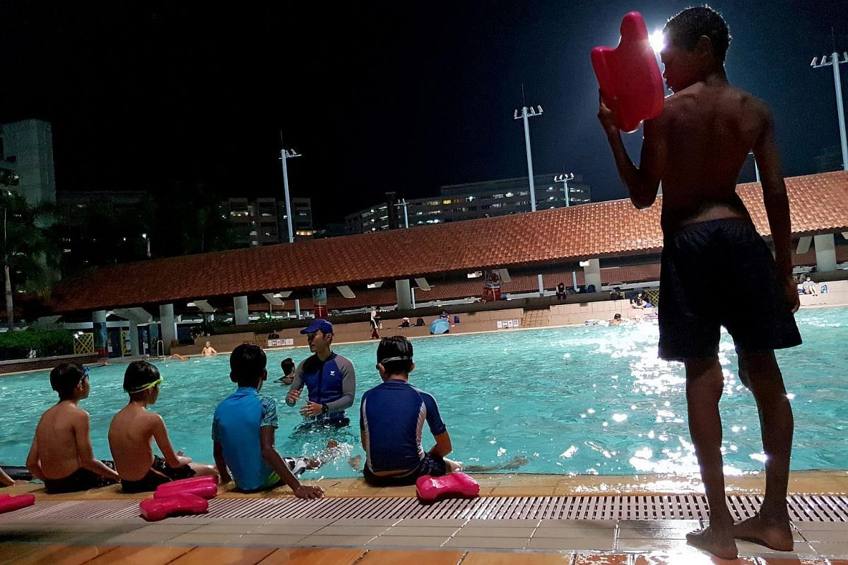 A boy prepares himself with his kickboard before entering the pool at Hougang Swimming Complex, as part of the SportCare's Swimming Programme.
