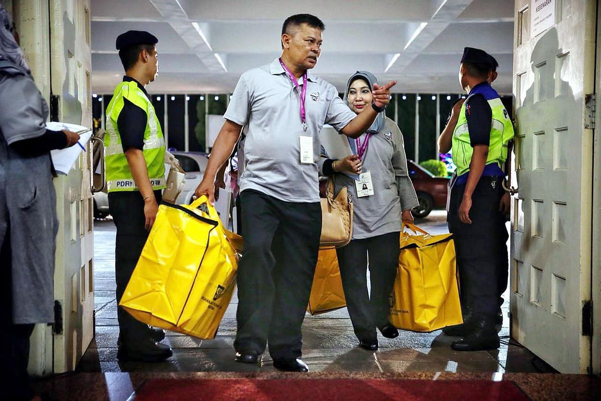 Staff carrying ballot boxes into Dewan Jubli Intan, a vote counting centre, in Johor Bahru on May 9, 2018.