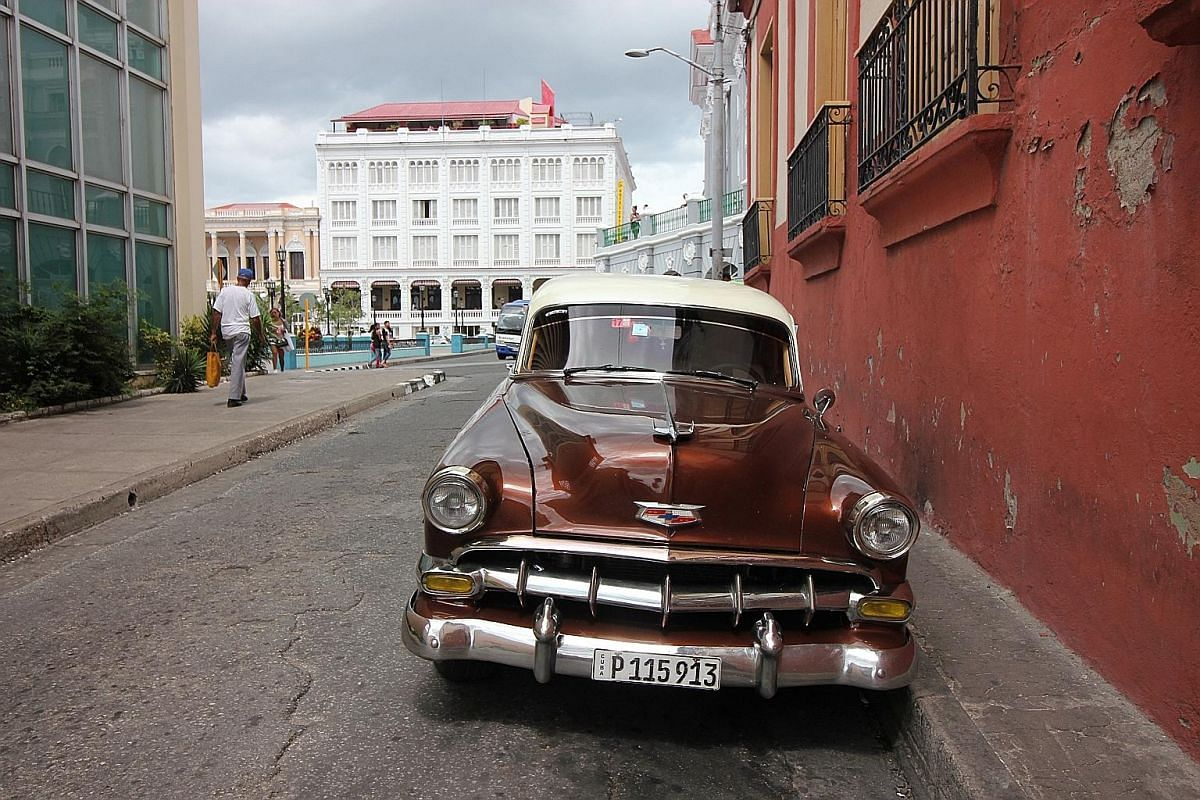 A vintage car (above) on a street off Parque Cespedes in Santiago de Cuba. People crossing streams in the Yumuri gorge (left). The Padre Pico stairs in Santiago de Cuba.