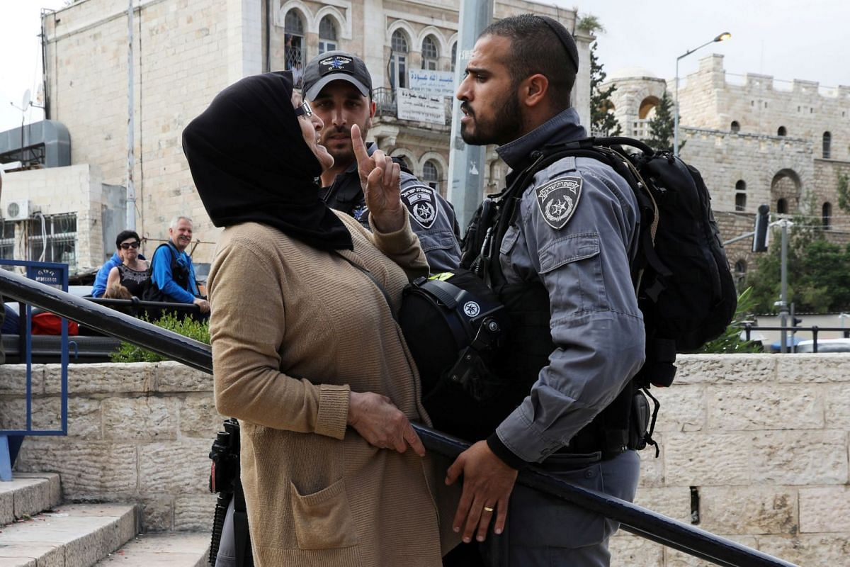 An Israeli police officer argues with a Palestinian woman outside Jerusalem's Old City's Damascus Gate, May 13, 2018. PHOTO: REUTERS