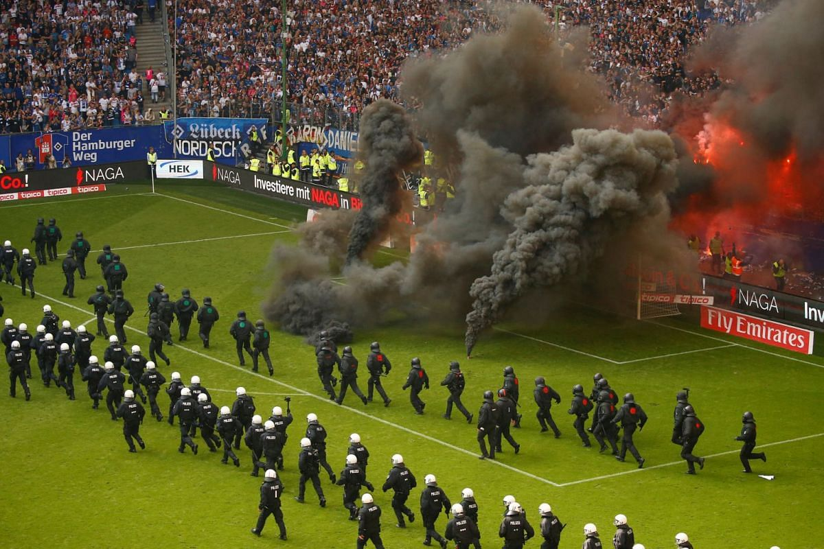 Hamburg fans let off flares and throw smoke bombs on to the pitch as riot police line up across the pitch during the Hamburger SV v Borussia Moenchengladbach soccer match at Volksparkstadion, Hamburg, Germany on May 12, 2018. PHOTO: REUTERS