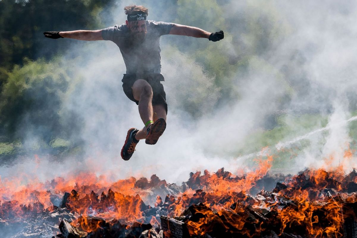 A man crosses the Fire obstacle as he competes during the Tough Viking race on May 12, 2018 in Stockholm. PHOTO: AFP