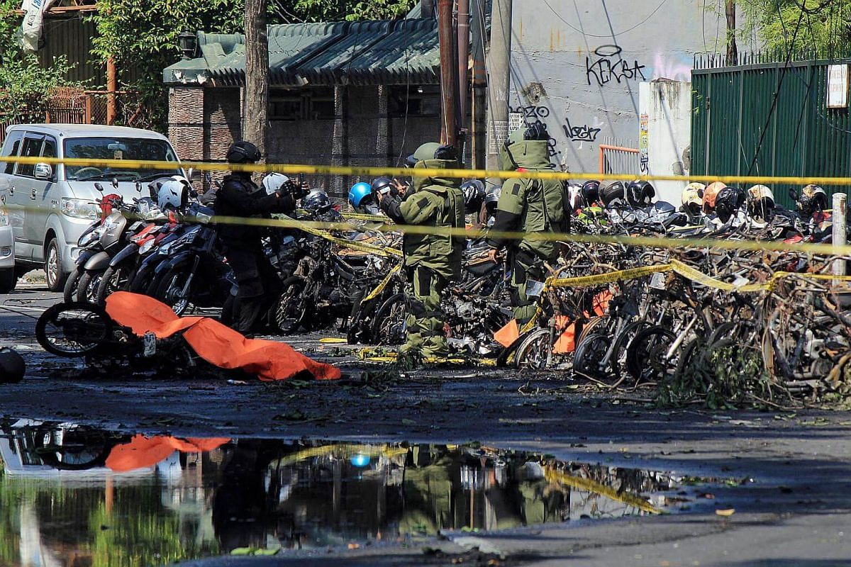 Indonesian bomb squad police officers inspect a blast site in front of the church in Surabaya, on May 13, 2018.