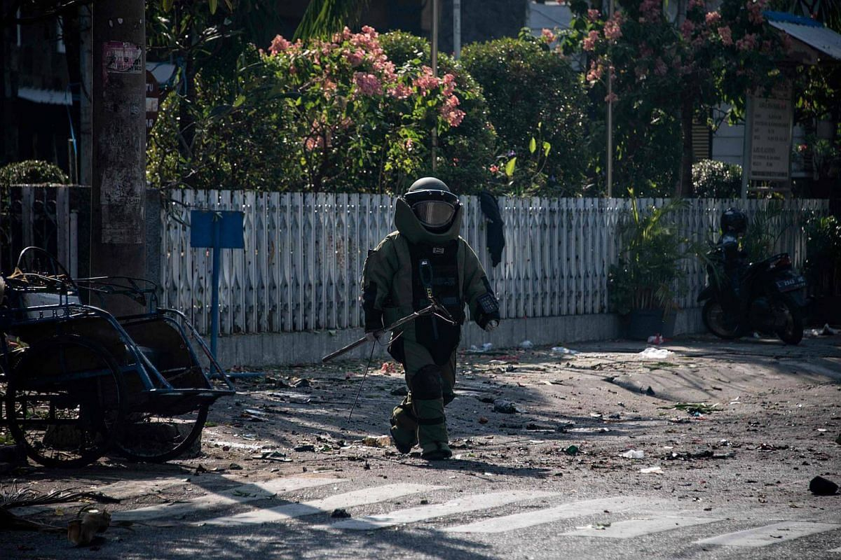 An Indonesian bomb squad member examining the site following a suicide bomb outside the church in Surabaya, on May 13, 2018.