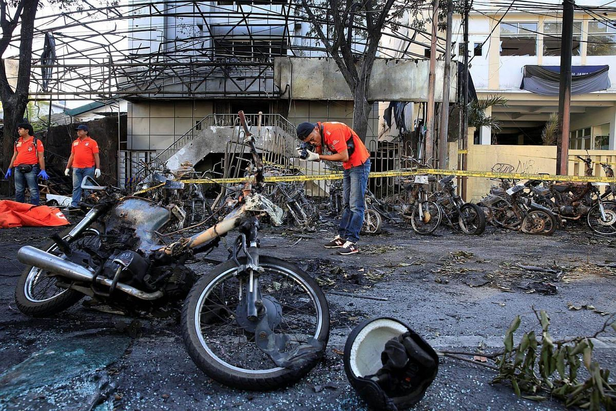 A forensic police officer taking pictures of debris near burnt motorcycles following a blast at the Pentecost Church Central Surabaya, in Indonesia, on May 13, 2018.