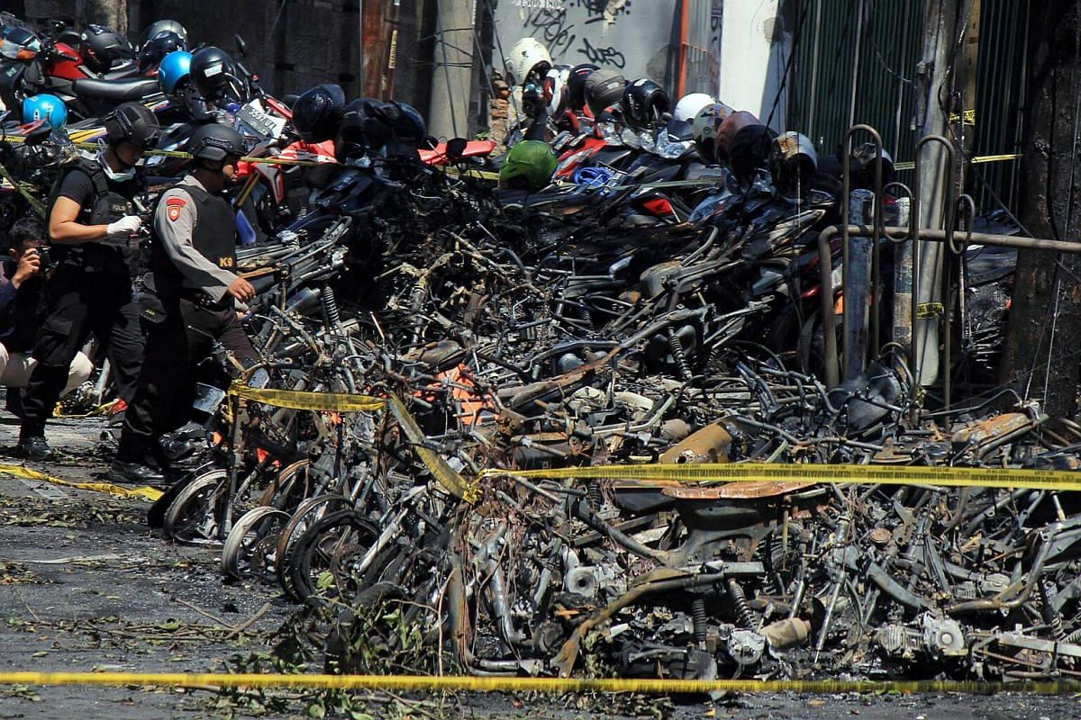 Burnt vehicles as Indonesian police officers inspect the site of a bomb blast in front of the church in Surabaya, East Java, on May 13, 2018.