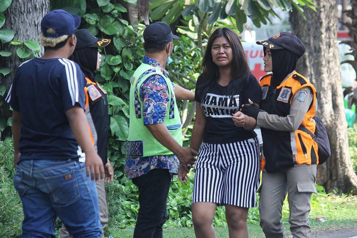Police assisting a woman looking for family members near the site of a blast at the Pentecost Church Central Surabaya, on May 13, 2018.