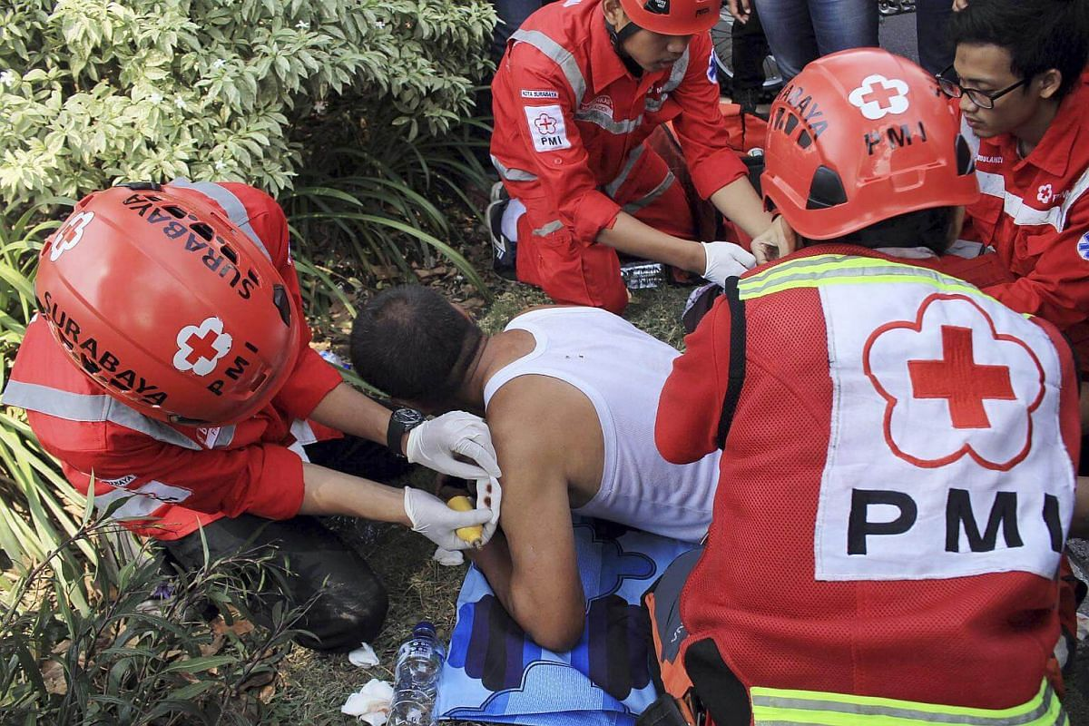 Indonesian paramedics giving medical treatment to a person who was injured in a bomb blast outside the church in Surabaya, on May 13, 2018.