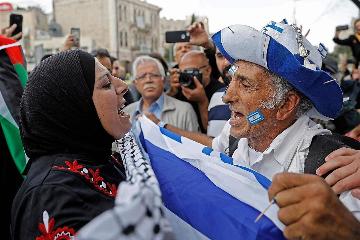 Left: An Israeli man confronts a Palestinian woman in Jerusalem as Israeli settlers celebrate Jerusalem Day.Far left: A Palestinian protester throwing away leaflets dropped by the Israeli military at the Israel-Gaza border yesterday. Above: Palestini