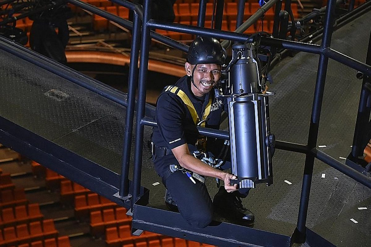 Mr Mohamad Azwan Mazlan adjusting light fixtures on the catwalk at the Star Performing Arts Centre