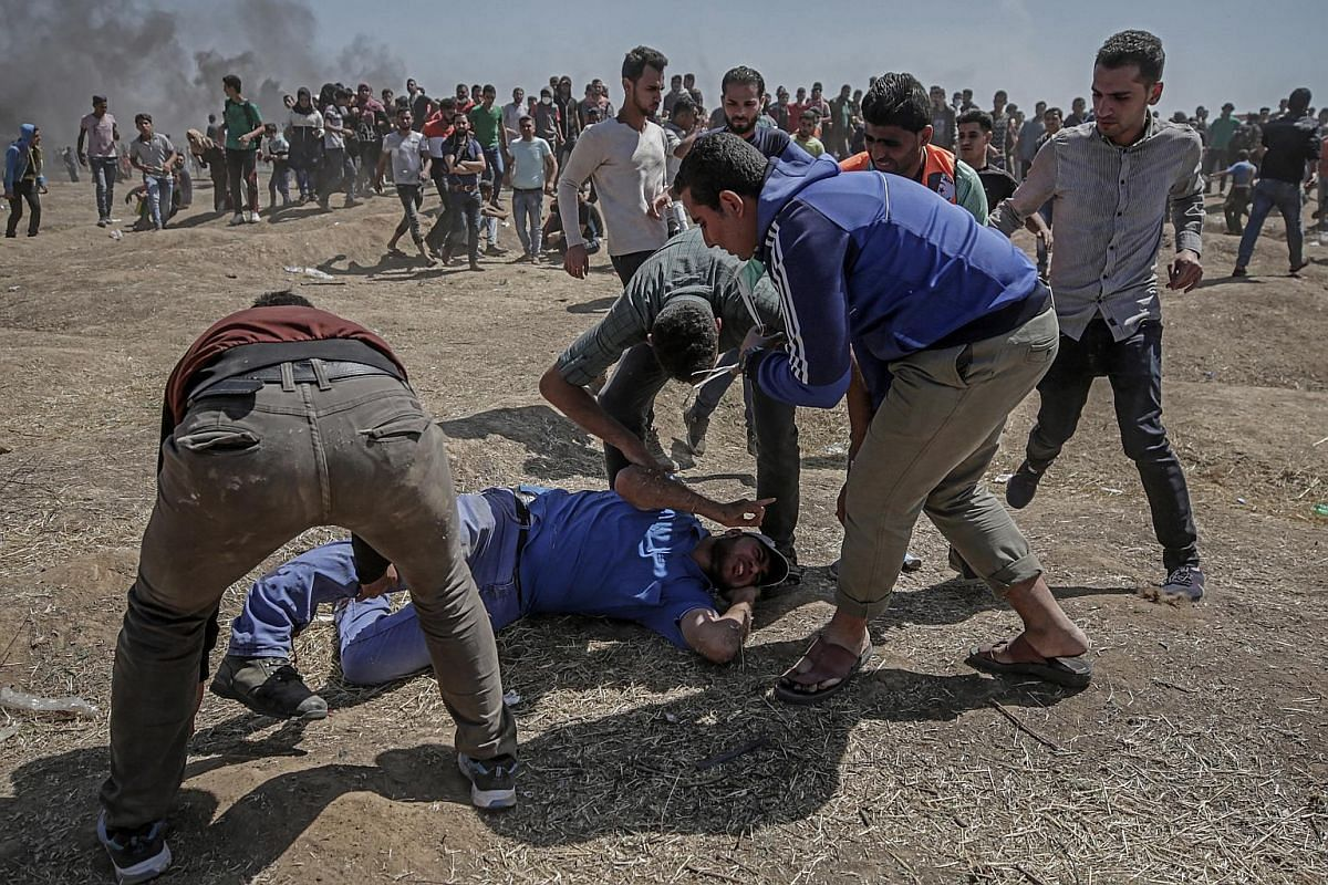 Palestinian protesters try to help a wounded man during clashes after protests near the border with Israel in the east of the Gaza Strip on May 14, 2018.