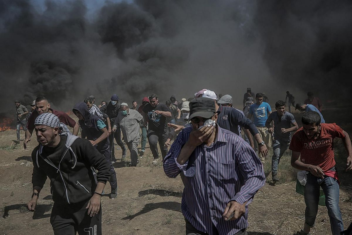 Palestinian protesters run for cover from tear gas fired by the Israeli army on May 14, 2018.