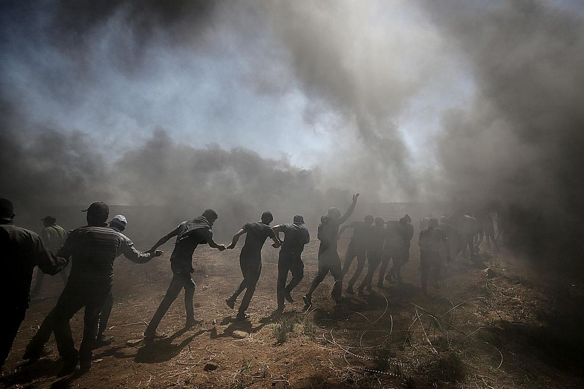 A line of Palestinian protesters beside barbed wire installed by the Israeli army.