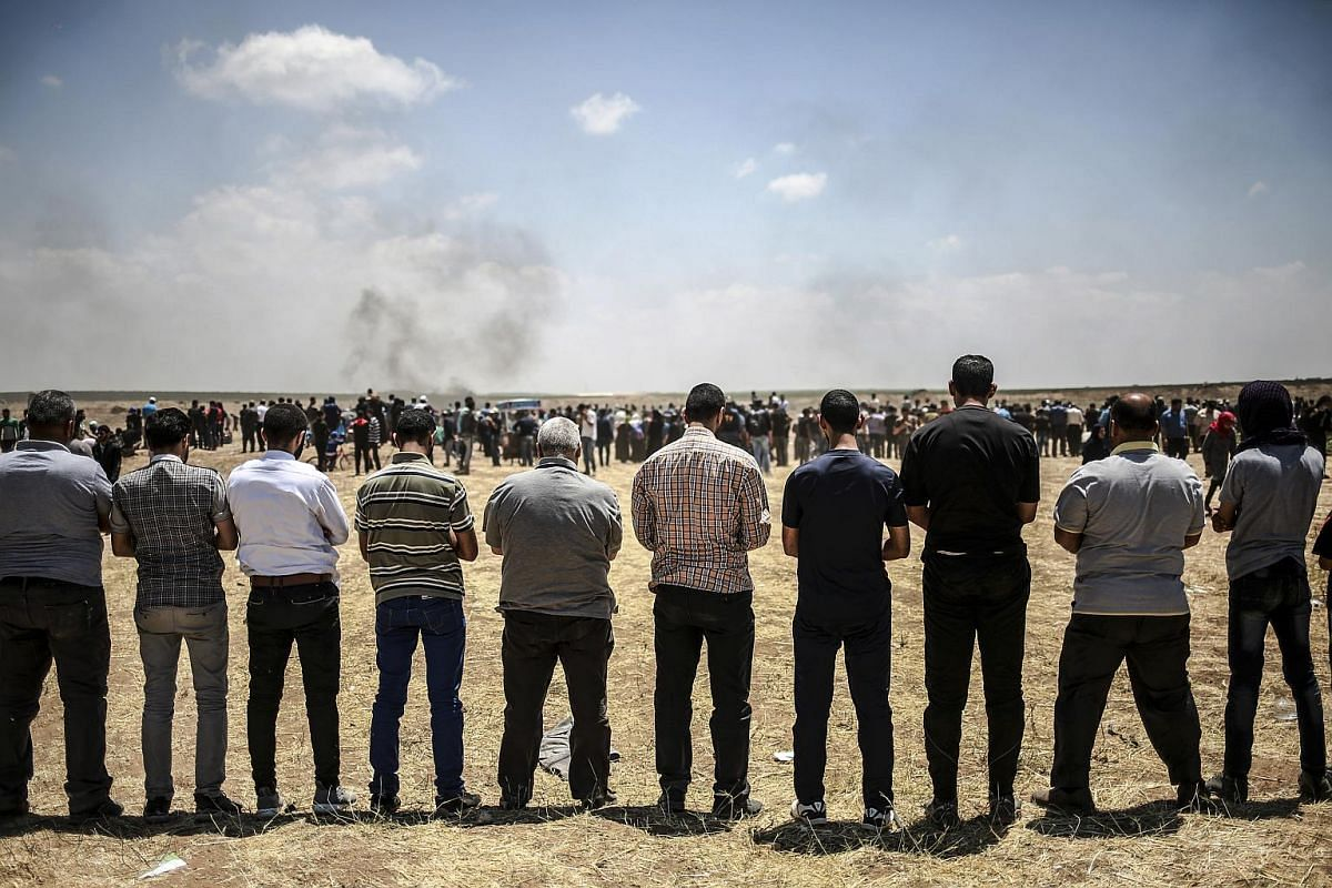 Palestinian protesters praying along the border with Israel on May 14, 2018.