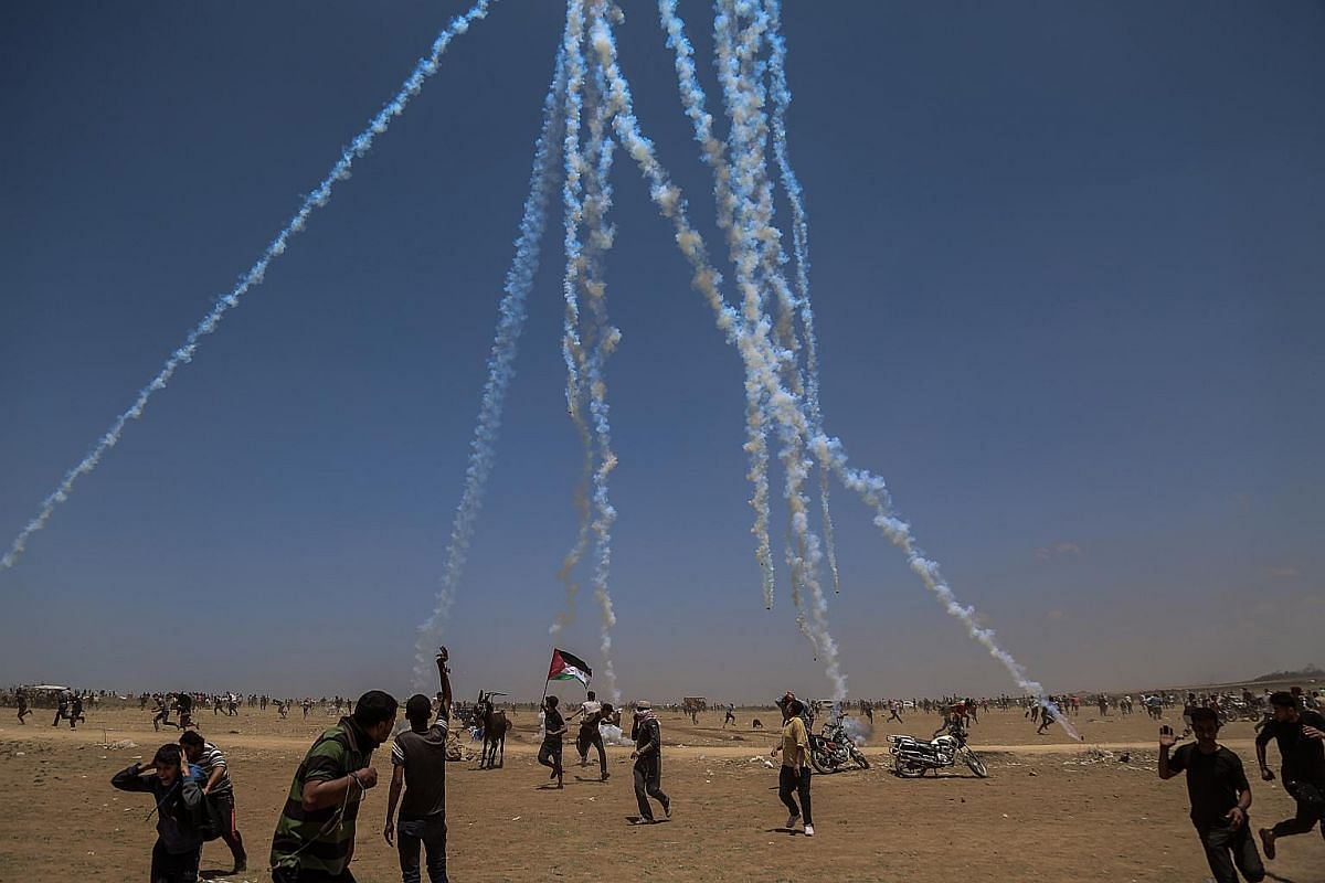 Tear gas canisters being hurled onto Palestinian protesters by the Israeli army.