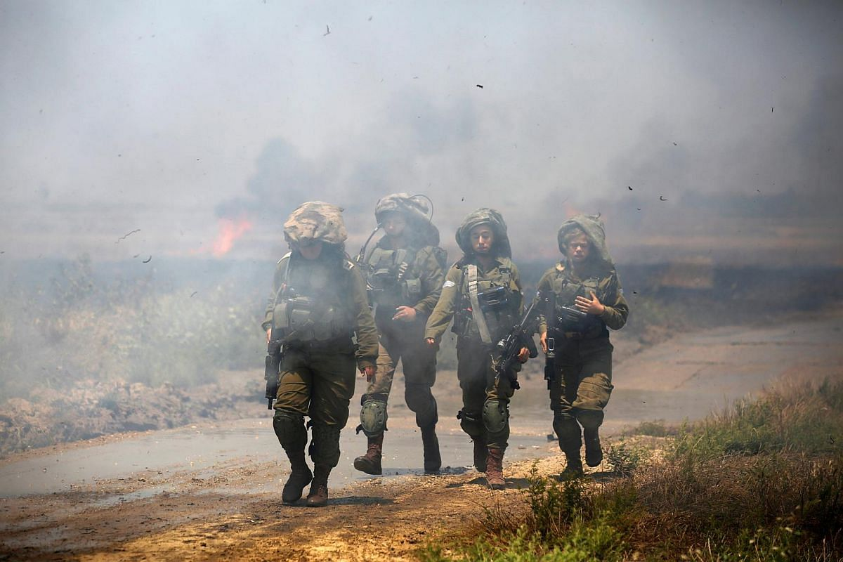 Israeli soldiers patrolling near a burning field near the border with Gaza on May 14, 2018.