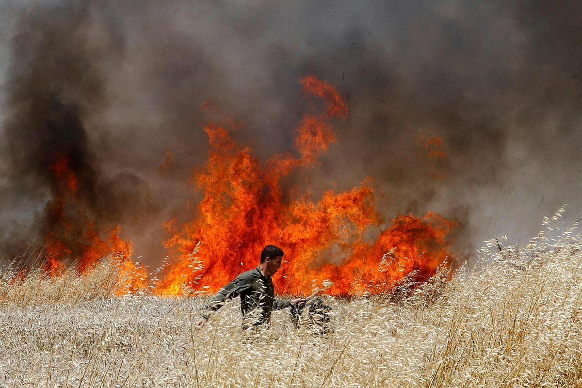 An Israeli soldier attempting to extinguish a fire in a wheat field near the Kibbutz of Nahal Oz, along the border with the Gaza strip on May 14, 2018.