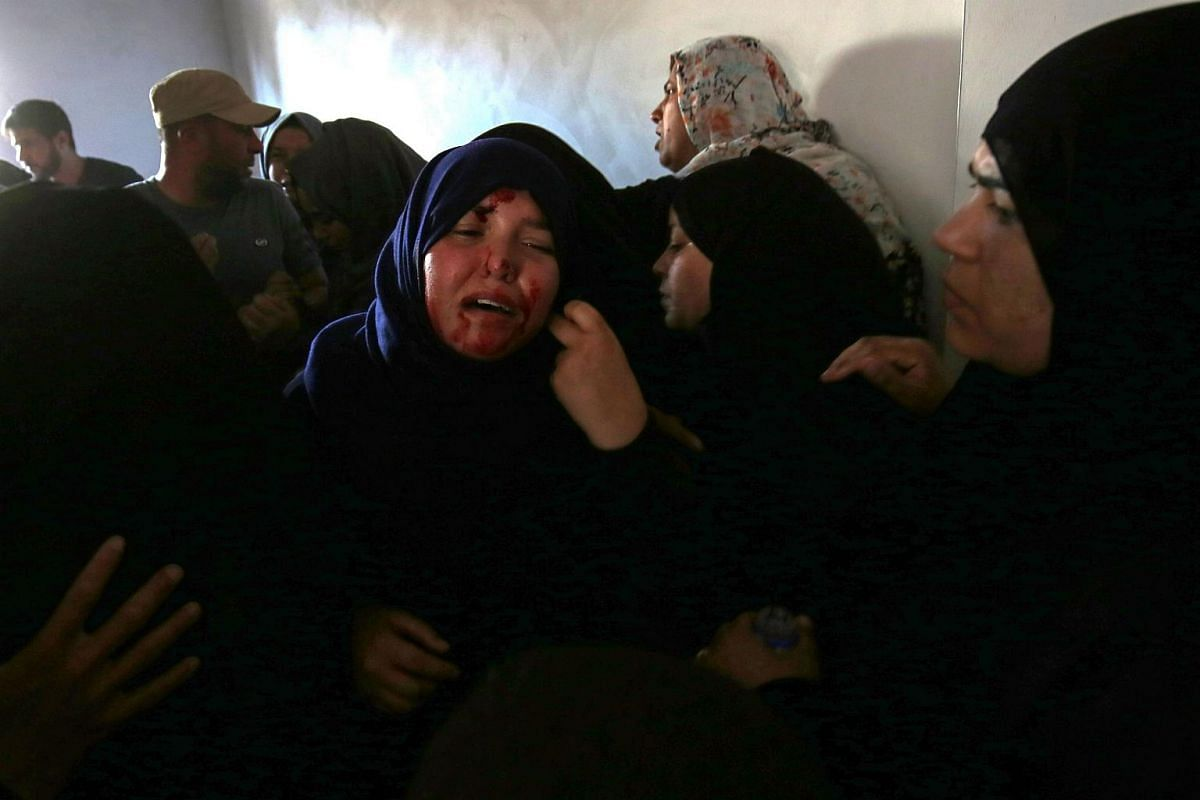 The sister of Palestinian Mahmoud Abu Taima, who was killed during a protest at the Israel-Gaza border, is seen with traces of her brother's blood on her face, during his funeral.