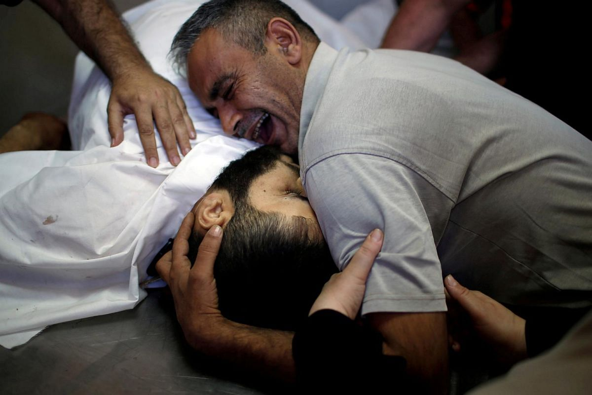 The brother of Palestinian Shaher al-Madhoon, who was killed during a protest at the Israel-Gaza border, reacts over his body at a hospital morgue in the northern Gaza Strip on May 14, 2018.