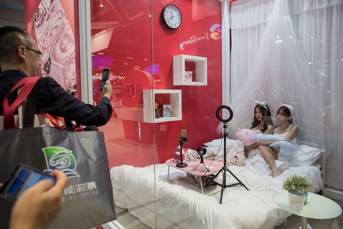 Two influencers sit in a bed behind glass while broadcasting live streaming at an exhibitor booth during the G2E Asia Conference in Macau, China, May 15, 2018. PHOTO: EPA-EFE