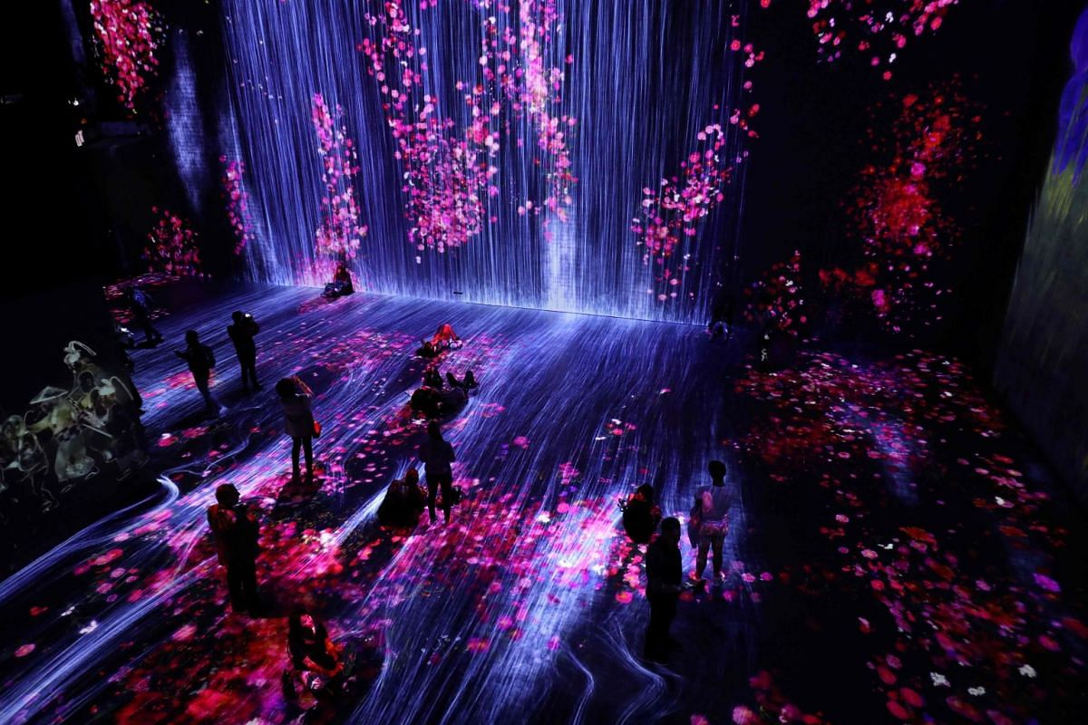 People enjoy the Teamlab show, an interactive digital show created by an interdisciplinary group of artists, engineers, 3D creators, mathematicians, architects and web designers at the Grande Halle de la Vilette exhibition hall on May 15, 2018 in Par