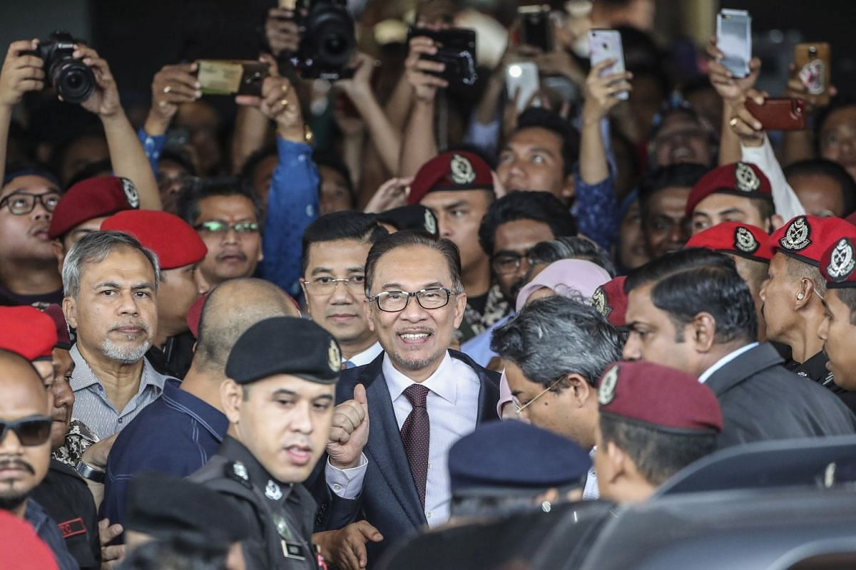 Malaysia's former deputy prime minister Anwar Ibrahim (centre) greeting the media after walking out of the Cheras Rehabilitation Hospital in Kuala Lumpur at 11.30am on May 16, 2018.