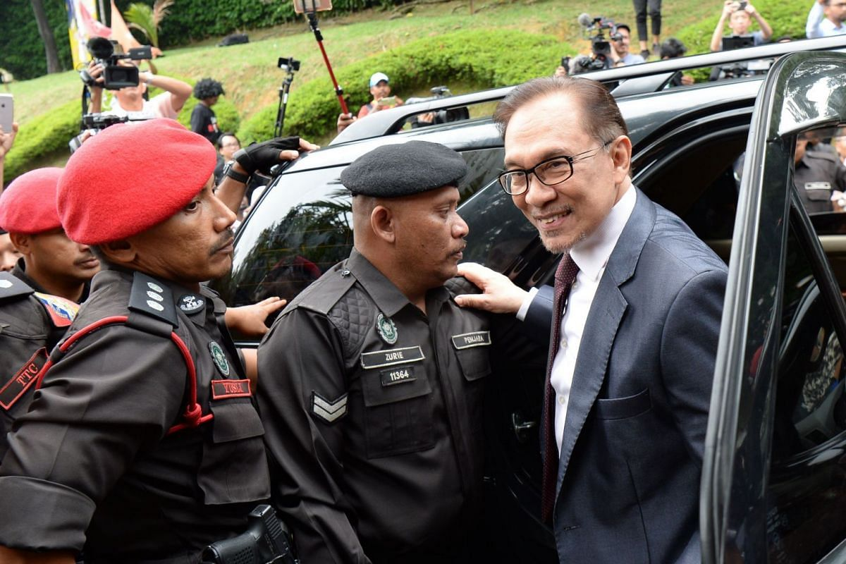 Jailed former opposition leader and current federal opposition leader Anwar Ibrahim (right) arrives at his house following his release from hospital in Kuala Lumpur, on May 16, 2018.