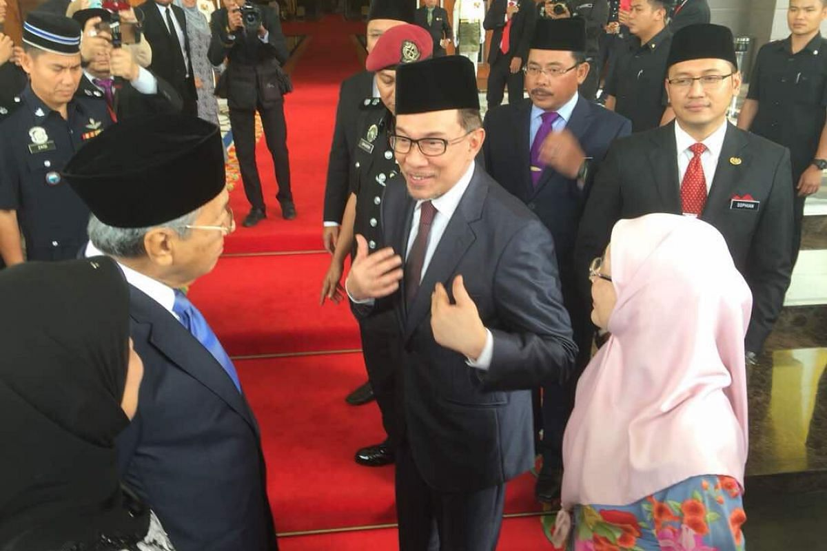 Mr Anwar Ibrahim (centre) speaking to Prime Minister Mahathir Mohamad at the palace, where he has been granted an audience with the King at noon.