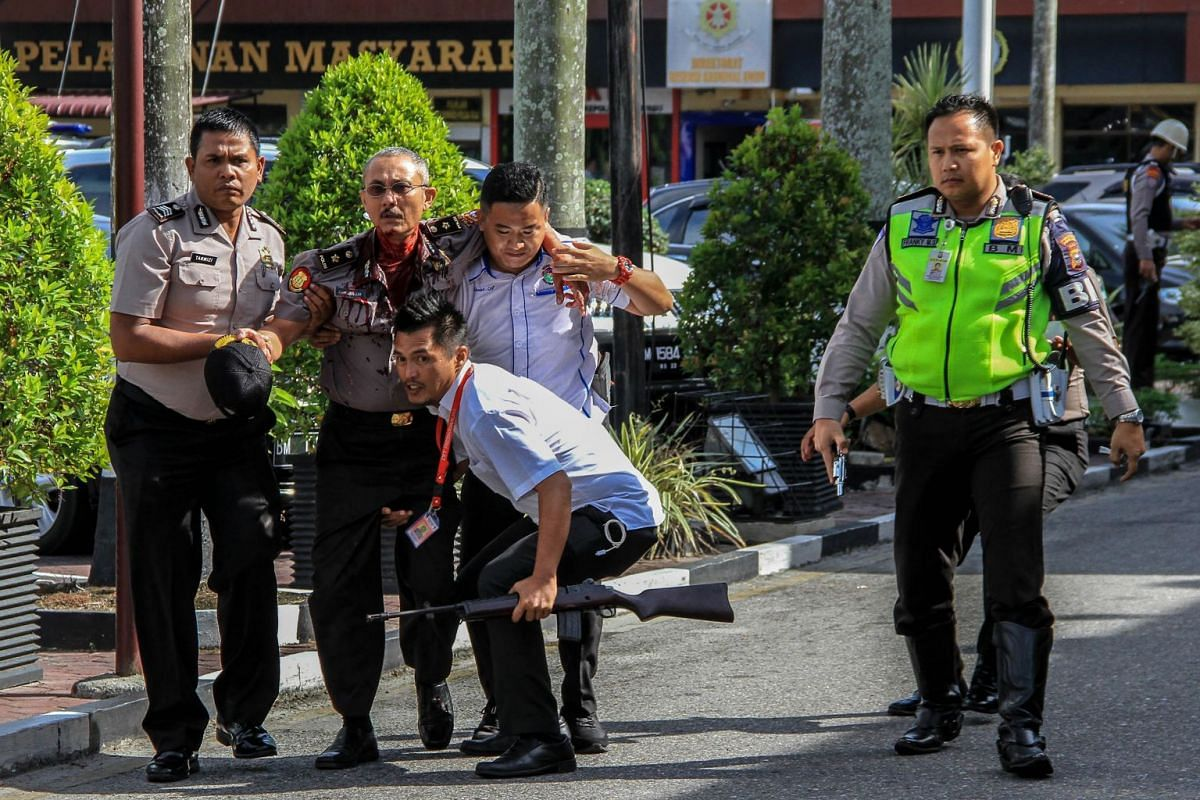 Police help an injured colleague after an attack on the police headquarters in Pekanbaru, Indonesia, on May 16, 2018. PHOTO: AFP