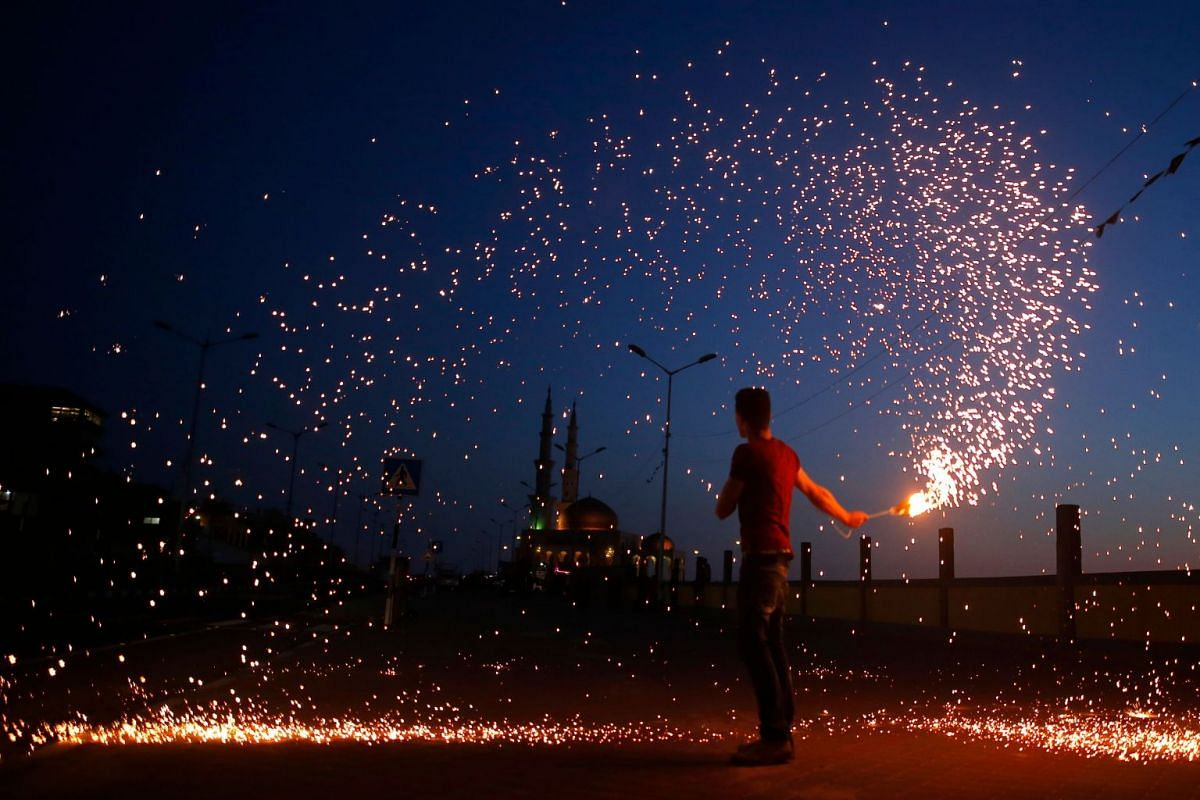 A Palestinian youth waves a sparkler next to a mosque in Gaza City on May 16, 2018, as the faithful prepare to start the Muslim holy fasting month of Ramadan. PHOTO: AFP