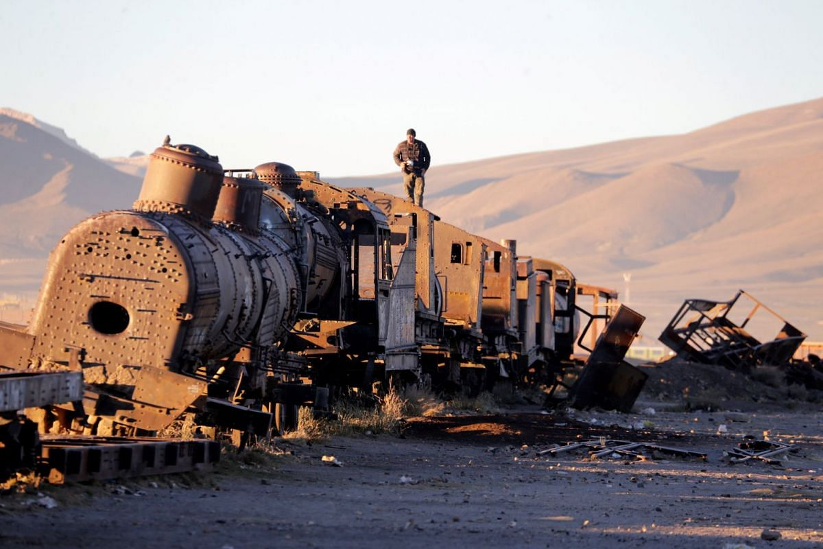 A photo released on May 17, 2018 shows a man standing on an old train of Bolivian Railways Company from 1870-1900 at the train cemetery in Uyuni, Potosi, Bolivia, May 11, 2018. PHOTO: REUTERS
