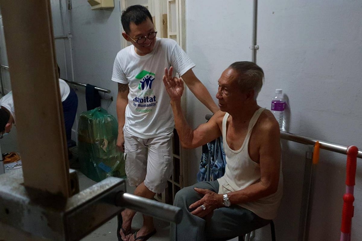 Volunteer from Habitat for Humanity, Thomas Lim Kia Hwee, 46 having a conversation with Mr Siew Tuck Choon, 80.