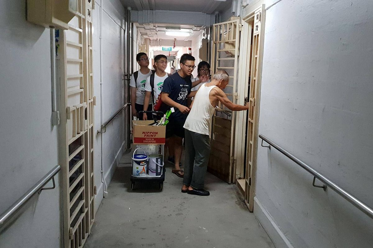 Mr Siew opening the door to his rented flat for the volunteers from Habitat Singapore.