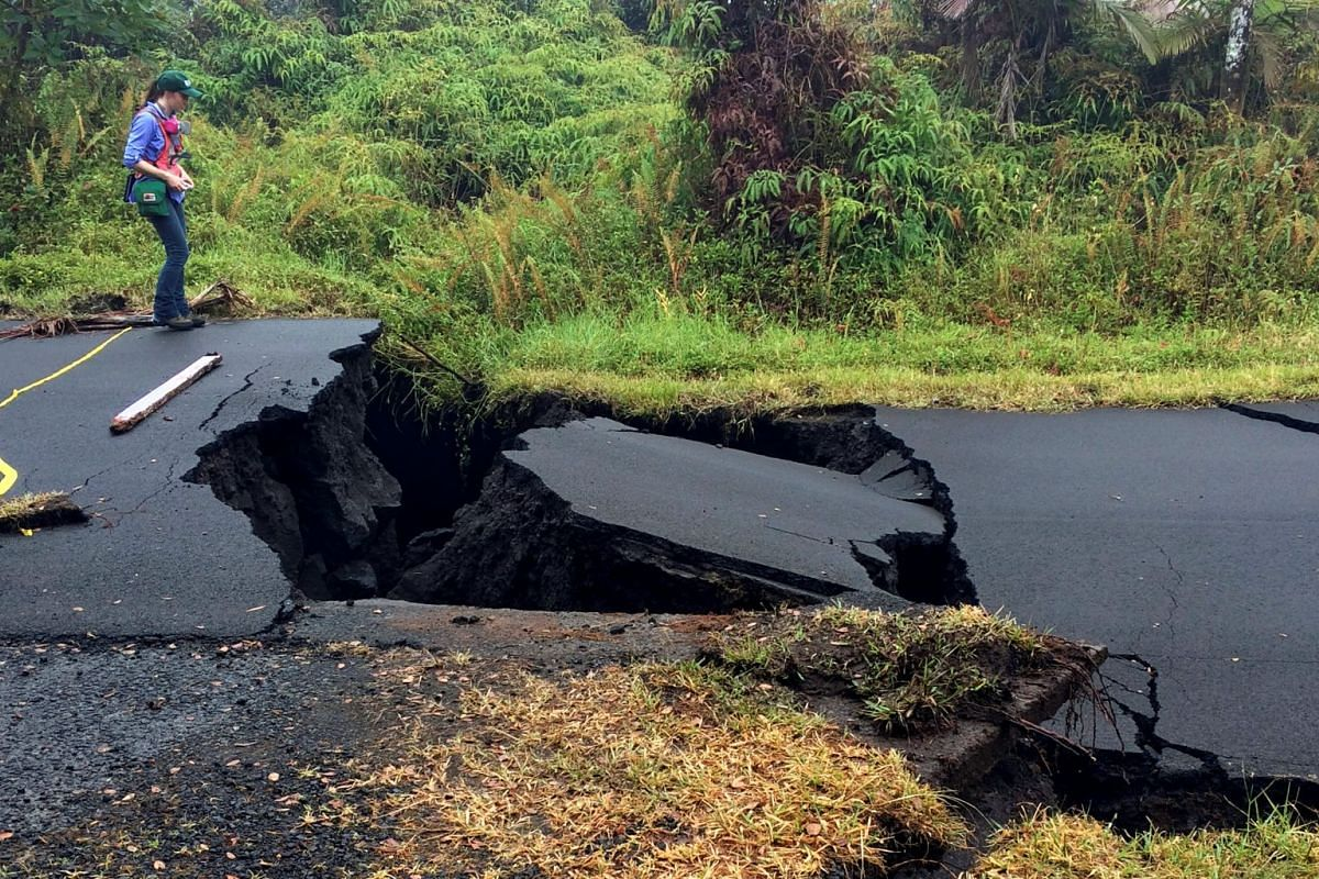 A geologist inspects cracks on a road in Leilani Estates, following eruption of Kilauea volcano, Hawaii May 17, 2018. PHOTO: USGS HANDOUT VIA REUTERS