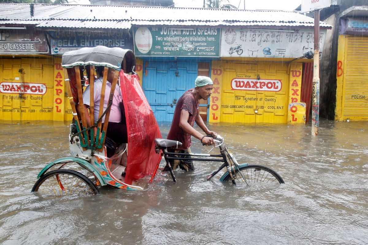 A man paddles his rickshaw as he helps a passenger wade through a water-logged street during heavy rains in Agartala, India May 18, 2018. PHOTO: REUTERS
