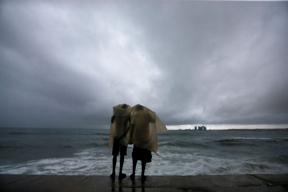 Two men use a plastic sheet to protect themselves from heavy monsoon rain as they stand by the sea in Colombo, Sri Lanka May 17, 2018. PHOTO: REUTERS